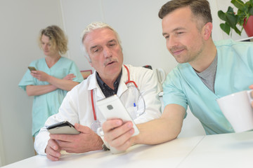 doctors with mobile phone in hands in office