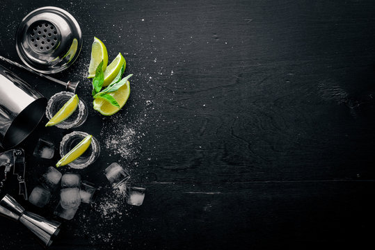 Tequila with lime and ice, on a black wooden surface. Top view. Free space.