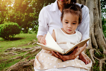 Mother and little girl reading a book under big linden tree.