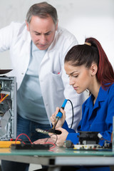 teacher supervising student soldering mother board of computer