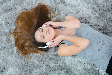 Woman layed on carpet listening to headphones