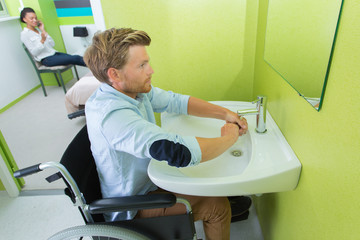 wheelchair user washing hands at a toilet for wheelchair users