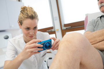 female doctor taking a picture of an injured knee
