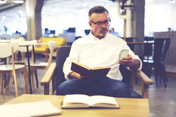 Concentrated male entrepreneur enjoying leisure time reading books while controlling work of his company chatting with administrative manager via smartphone and wifi being up to date with situation