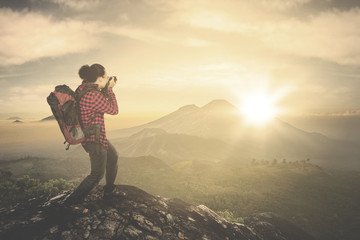 Man taking photo of sunrise view on mountain