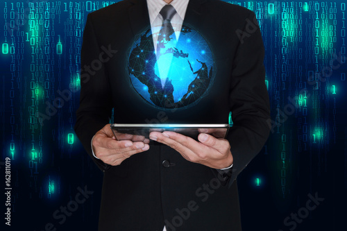 Businessman hand hold tablet and glowing light blue world on matrix businessman hand hold tablet and glowing light blue world on matrix digital background as business voltagebd Gallery