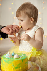 little baby birthday one year girl crushing her yellow cake
