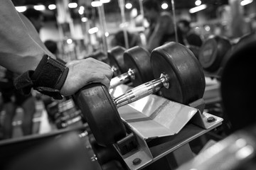 Black and white images Hand holding dumbbell in the gym bodybuilding.
