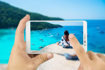 Taking photo with mobile smart phone,Women scenic ride Beautiful sea and blue sky at Similan island,Thailand.