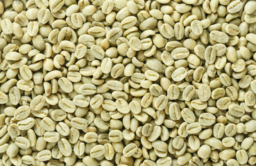 Unroasted green Arabica coffee beans flat surface. Backgrounds. Closeup macro food photo directly from above.