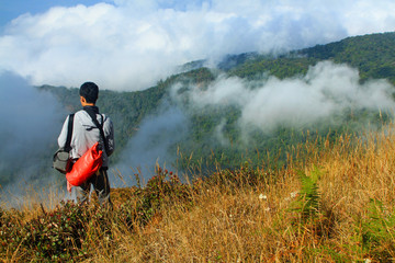 Asian man standing, carrying red bag and looking to nice vierw, blue sky, clouds and mist on the mountain view point