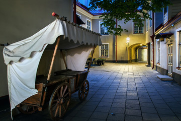 historical trading the car in a narrow street of the old town. Colorful, medieval small courtyard in Tallinn. Attraction in Estonia. White nights in the summer season.