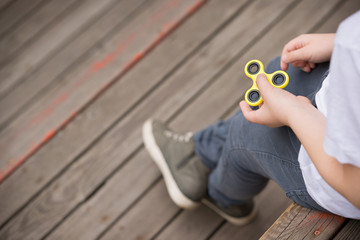 Kid boy sitting on wooden playground and playing with fidget spinner gadget - summer trend of 2017. Yellow hand spinner, fidgeting hand toy rotating on child's hand