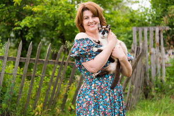 woman is holding cat against the background of rural fence