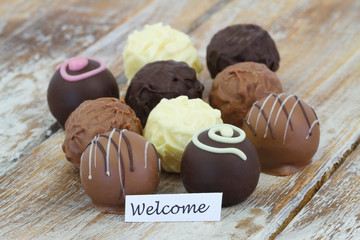 Welcome card with selection of chocolates and pralines on wooden surface
