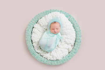 baby wrapped in blue blanket in basket, topview