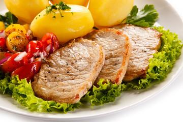 Grilled pork chops, boiled potatoes and vegetable salad