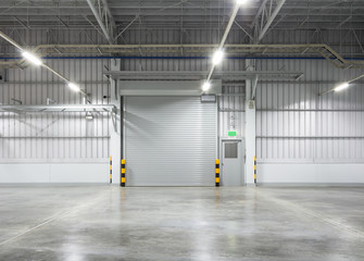 Roller shutter door and concrete floor inside factory building for industy background.
