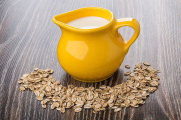 Yellow jug of milk and scattered rye flakes