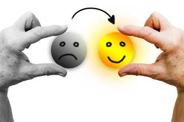The left hand of a woman in black and white holds a sad icon face. The right hand, in color, holds a happy smiling icon face, shining like the sun. An arrow goes from the sad icon to the happy one