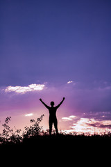 Silhouette of a man with raised-up arms at the beautiful sunset on the mountain on a purple background sky