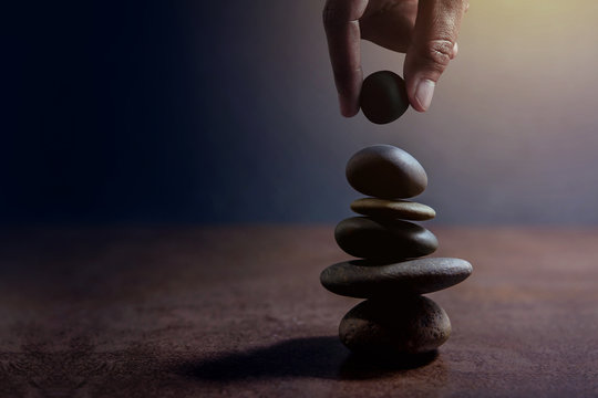Balance concept between of Life and work present by Hand setting a natural zen rock stone on Stack, Side view and Dark light