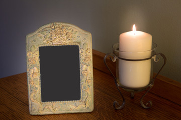 Decorative blank photo frame with lit candle on dresser