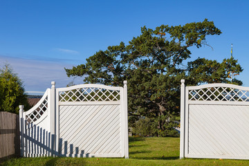 White garden wooden fence and gates to yard with green grass and trees