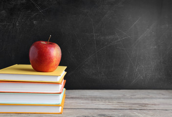 Books and apple on wooden table against school blackboard