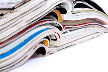 Plano cerrado de revistas y periodicos amontonados sobre fondo blanco. Información y comunicación sobre noticias