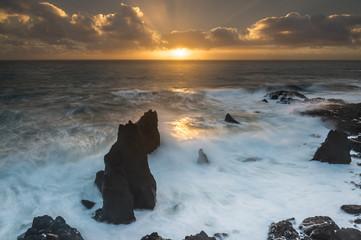 Faraglioni vulcanici e rocce sulla costa atlantica di Keflavik al tramonto, Islanda