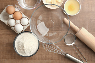 Bowl with flour and ingredients for dough on table
