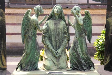 Woman and two angel girls Statue in Milan Monumental Cemetery