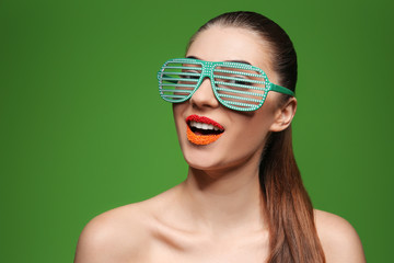 Portrait of beautiful woman with creative makeup and party glasses on color background