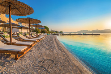 Beautiful view over the beach Nikiana with chairs, umbrellas and a heart drawing on sand, in Lefkada island, Greece