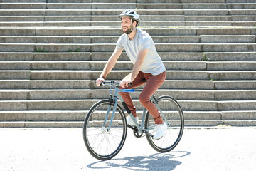 Handsome young man riding bicycle outdoors on sunny day Wall mural