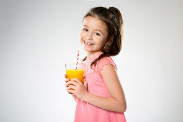 Cute little girl with glass of juice on light background