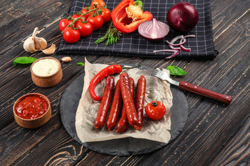 Composition with yummy grilled sausages on wooden table