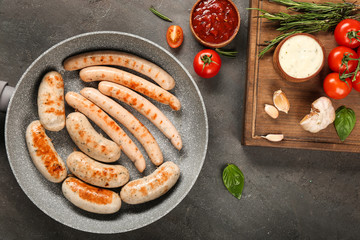 Grey frying pan with delicious grilled sausages on kitchen table, top view