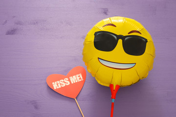 image of cute smiling emoticon wearing black sunglasses, emoji concept