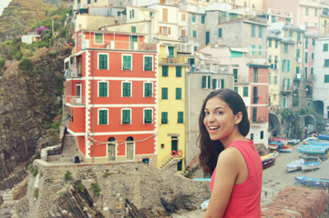 Beautiful red dressed girl smiling in Riomaggiore italian village of Cinque Terre, Italy. Vintage filter.