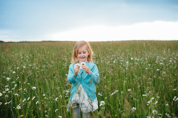 Little girl in a chamomile field