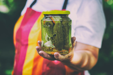Senior woman holding a jar of pickles in the garden. Homemade pickled cucumbers in a glass jar. Preserving jar of gherkins with mustard seeds and dill.