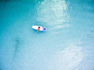 Aerial view of surfer surfing in ocean