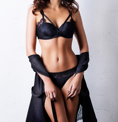 Young and beautiful fashion model posing in erotic lingerie over white background. Fashion, beauty, glamour concept.
