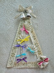 xmas conceprual image of christmas tree with bells ribbon bow and fans as decorations
