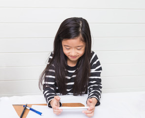 Cute asian girl kid happily watching video clip on the internet during her study time with smile on light background, selective focus