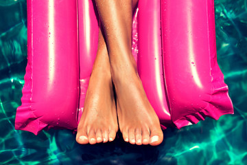 Tanned well-groomed feet in the pool on magenta inflatable mattress for swimming . Pedicure and foot Spa .
