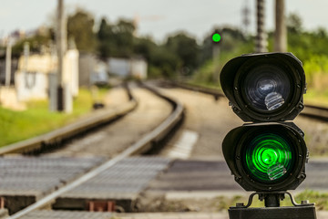 Routing traffic light with a green signal on railway. Railway crossing with semaphore. Permissive Motion. Limited depth of field. Fototapete