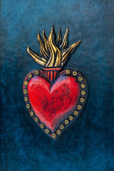 Red sacred heart on blue background